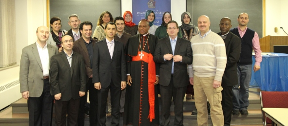 IDI members & volunteers break bread together with Cardinal Onaiyekan